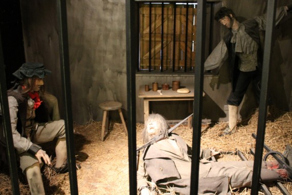 In this scene, Christian Harrison is awaiting transportation to Botany Bay, Australia, for 14 years. Edward Freeman, convicted of rape, is chained to the wall waiting to be hanged in the morning and James Thompson, the horse-stealer on the floor, is pinned there because he keeps trying to escape.